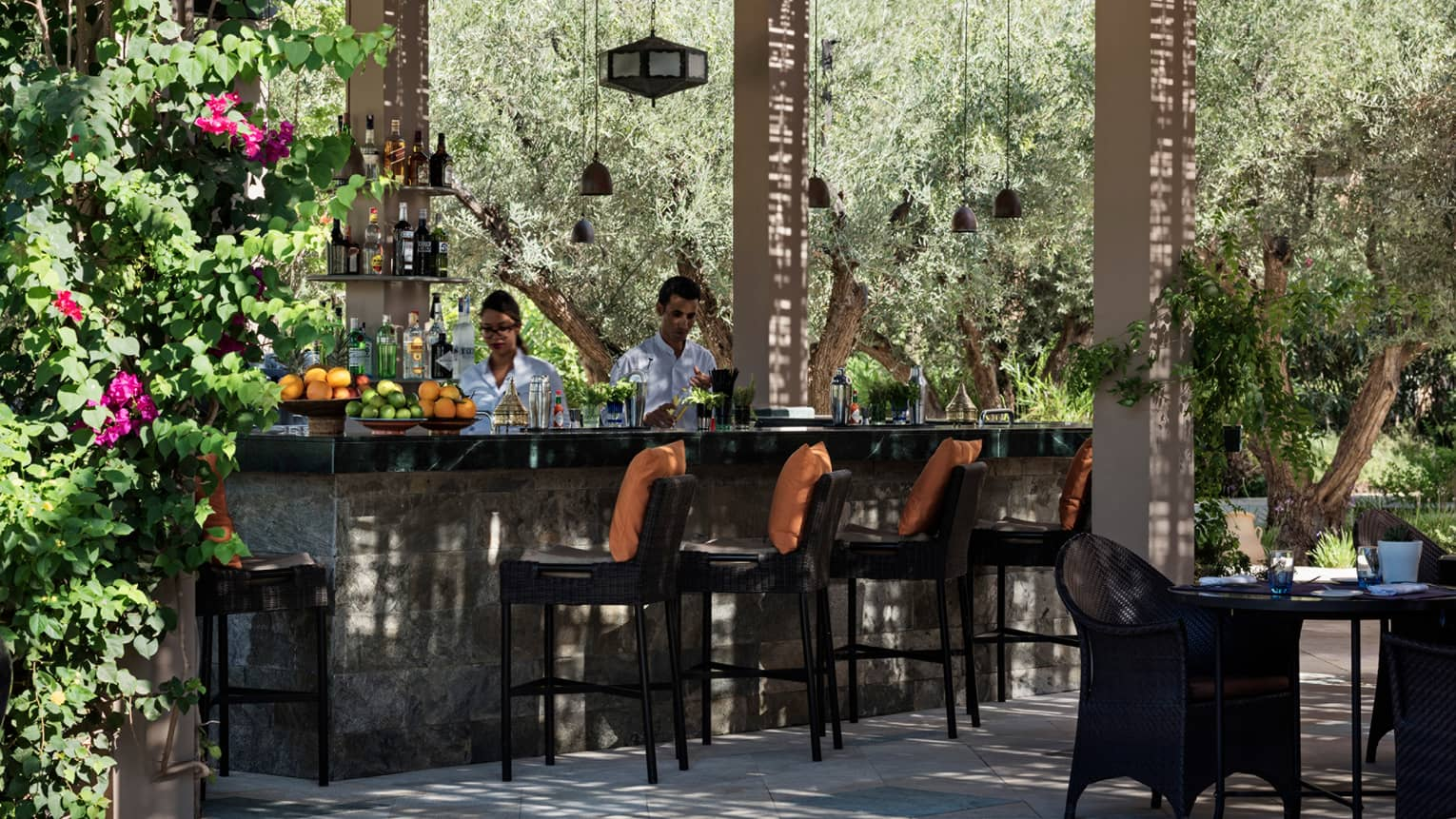 Bartenders mix cocktails at small outdoor bar on garden patio