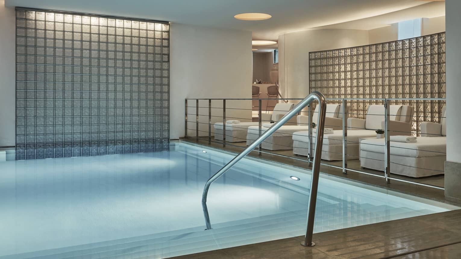 Railing into indoor spa pool under platform with white lounge chairs