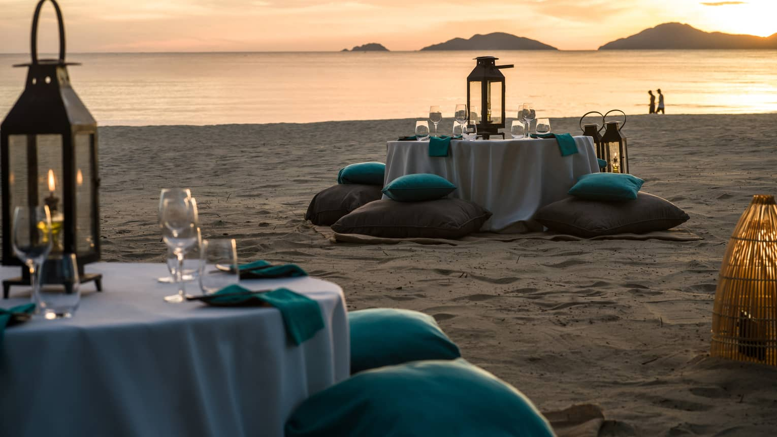 Two tables with white cloths, glasses, lanterns and turquoise cushions on sandy beach at dusk