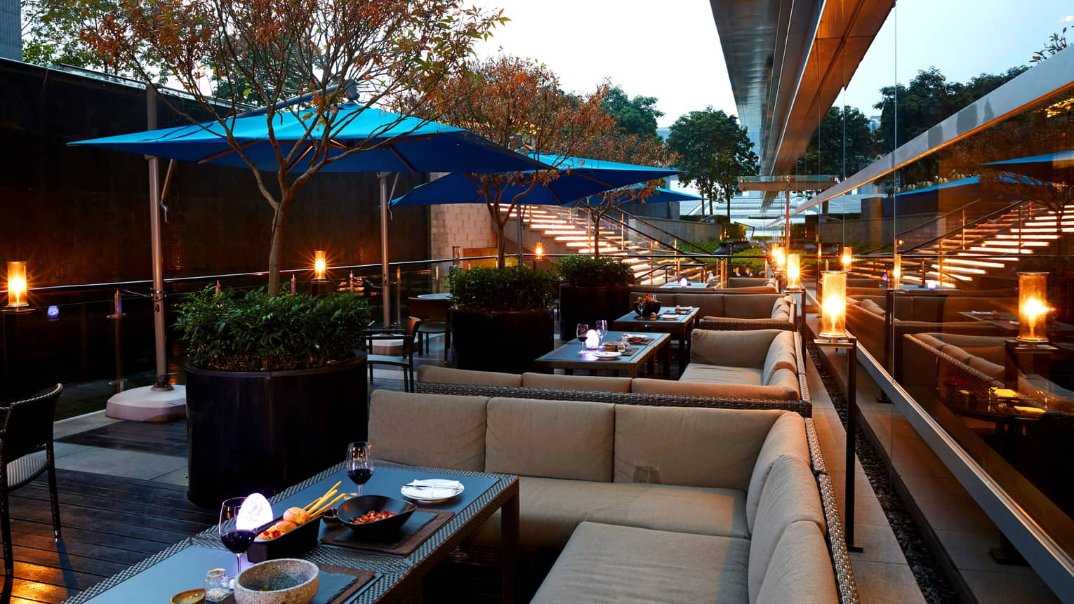 Foo rooftop patio lounge banquettes, potted trees, blue umbrellas
