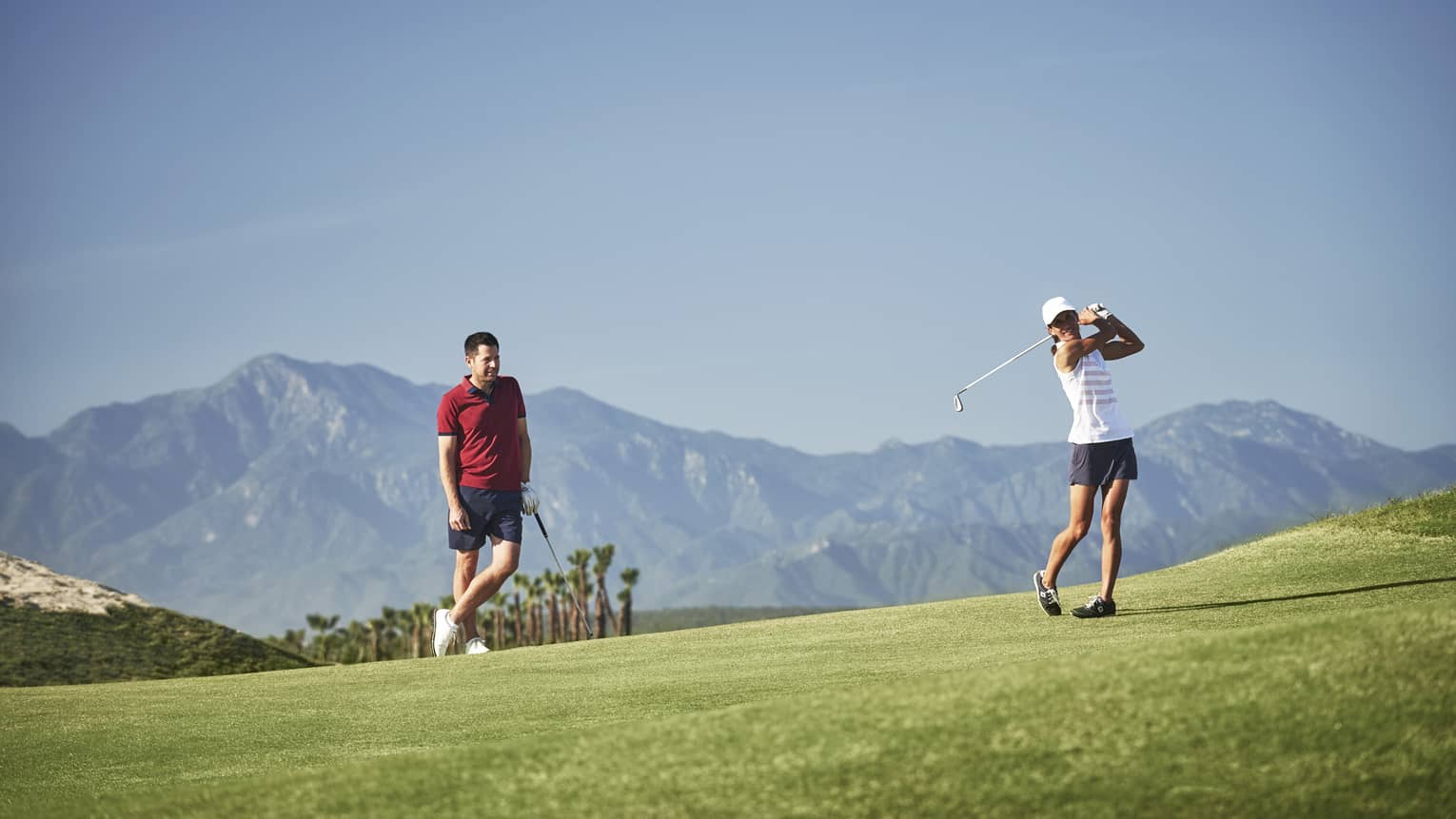 Woman swings golf club as man watches on green course, mountains in background