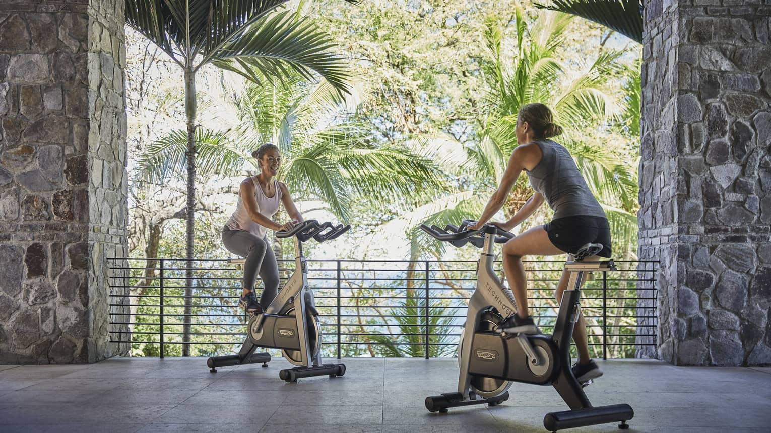 Two women on cardio bike machines face each other on stone patio in open-air fitness centre