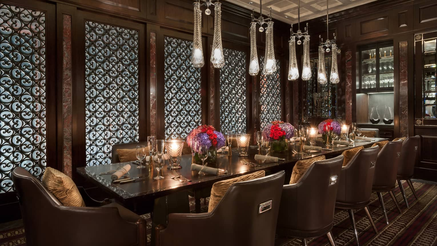 Long dining table in front of decorative wood screen wall, under long crystal lights
