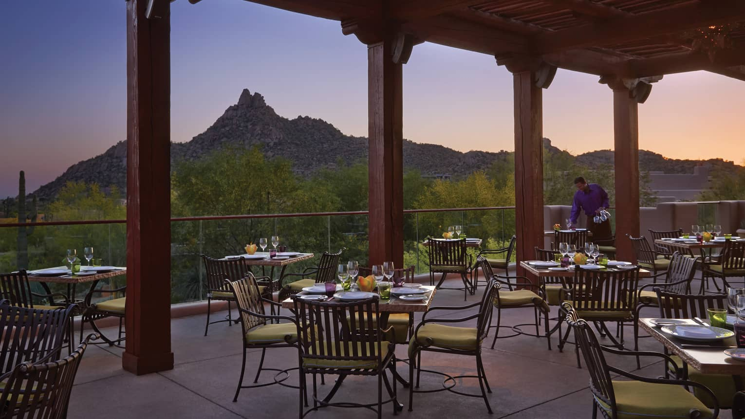 Patio dining tables under tall wood pergola, looking out at mountains, desert sunset