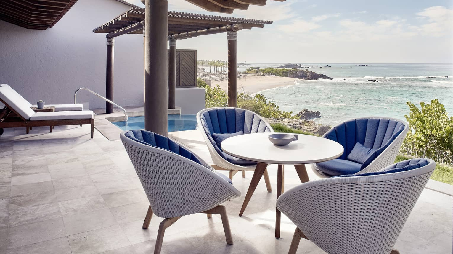Outdoor terrace, dining table with four wicker chairs, plunge pool, ocean view