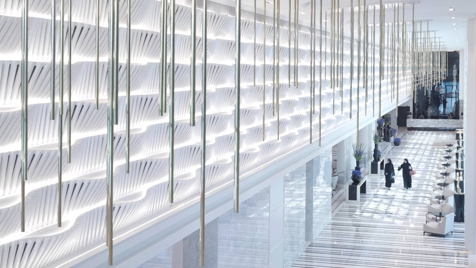 Looking down from illuminated white sculpture wall as two people walk in bright hotel lobby