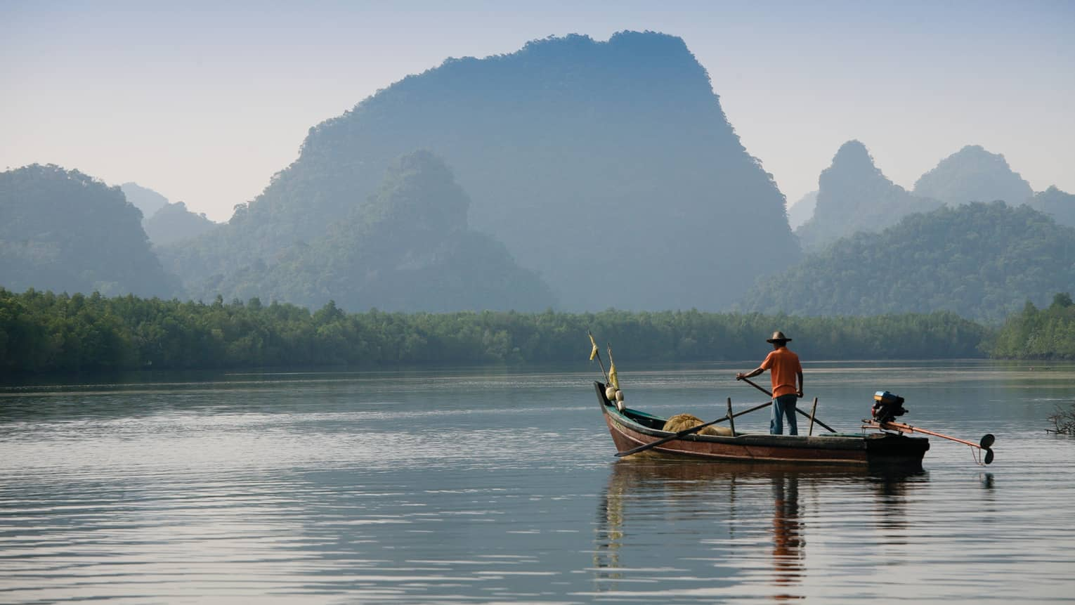 Man in a boat on Langkawi river with mountains in the background