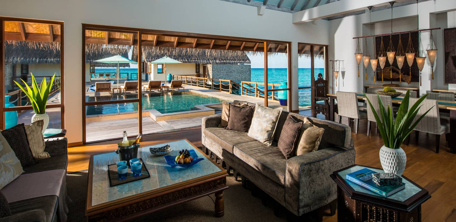 Three-Bedroom Land and Ocean Suite living room sofas around table with fresh fruit, beer on ice