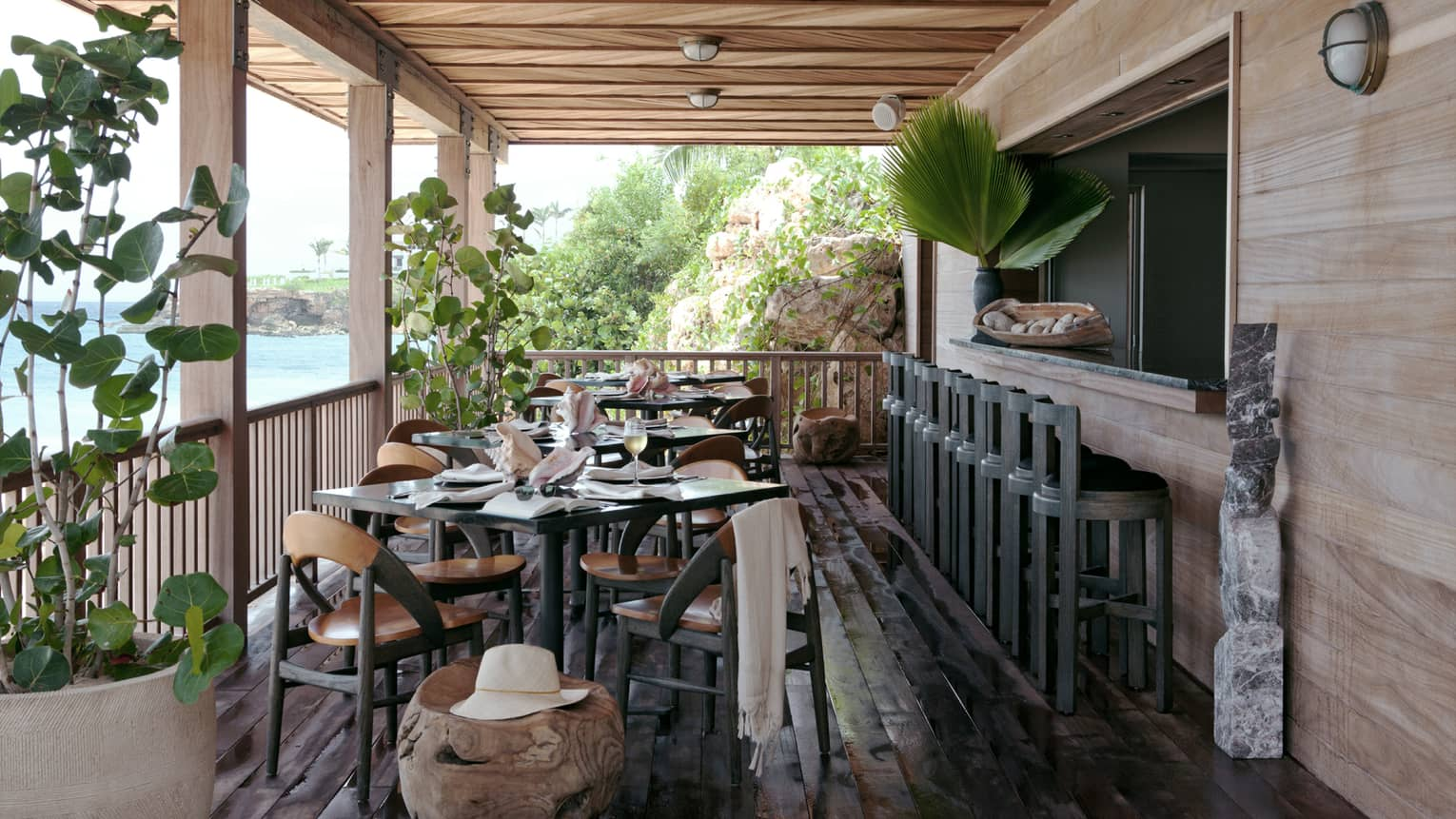 Cosy Half Shell Beach Bar table and chairs on small rustic wood porch, stools along bar, potted plants