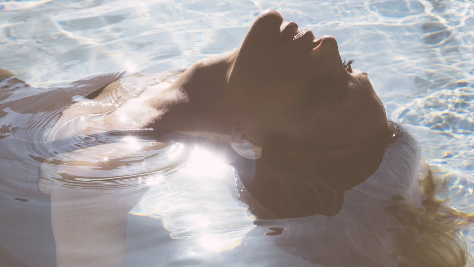 Close-up of woman's head as she floats on her back in pool, sunlight reflecting, her hair flowing in water
