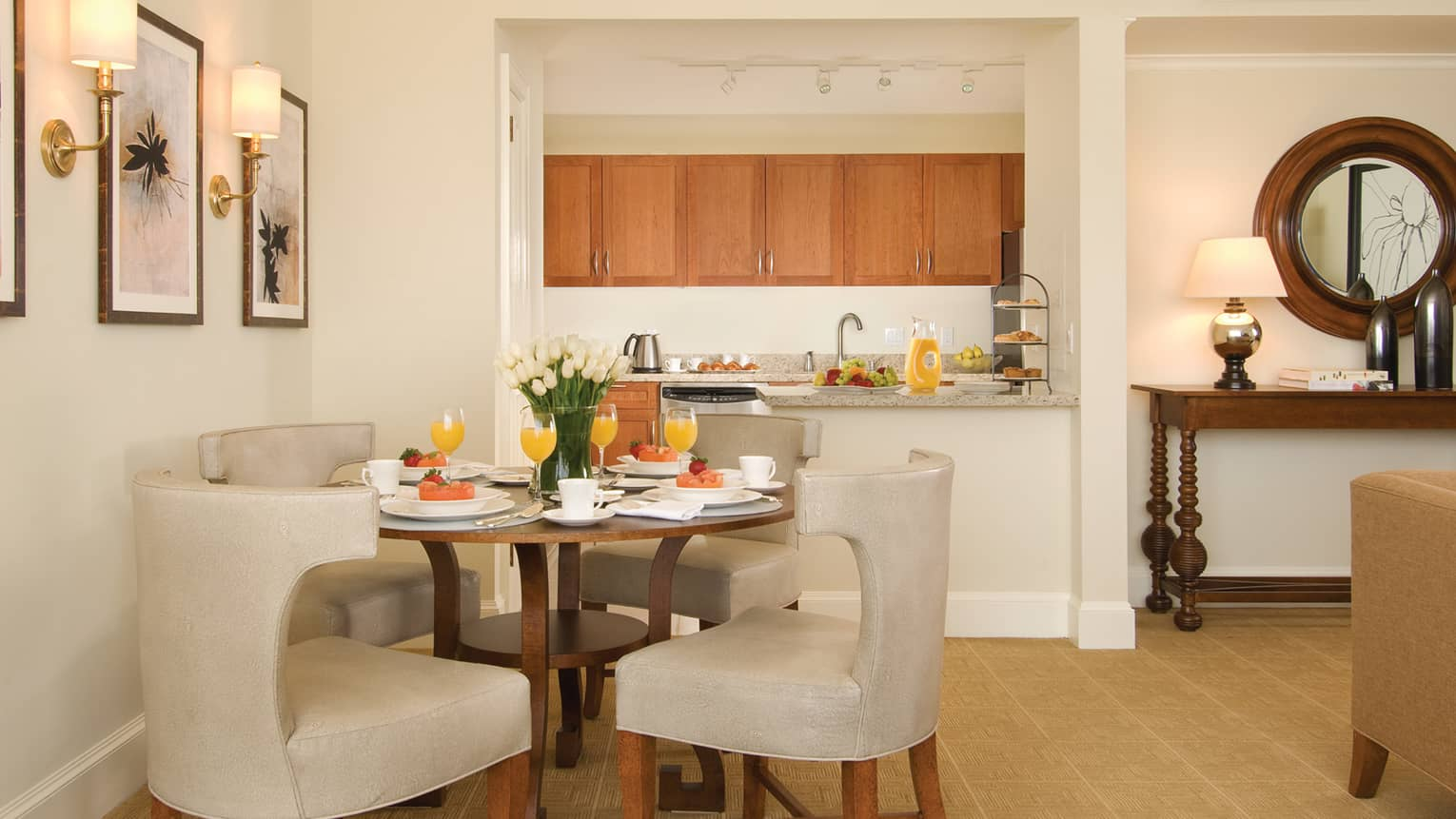 Wine glasses with orange mimosas, fresh fruit plates on round in-room dining table with white chairs