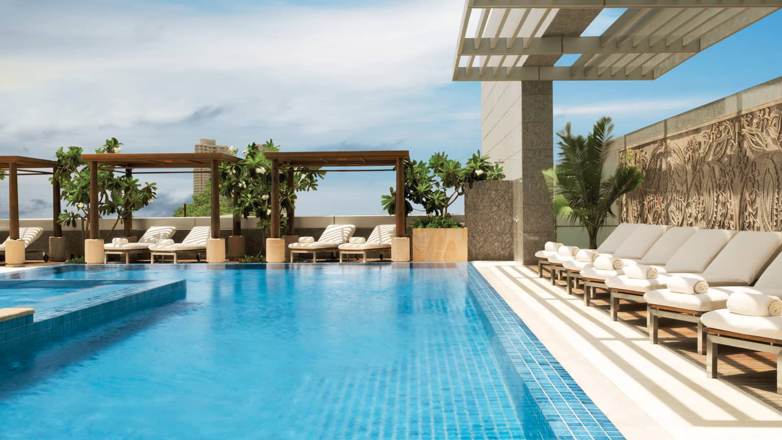 White lounge chairs under pergola by sunny outdoor swimming pool