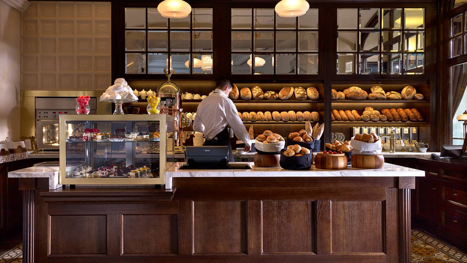 KOLLÁZS Brasserie & Bar bakery counter with breads, pastries, staff in front of bread display