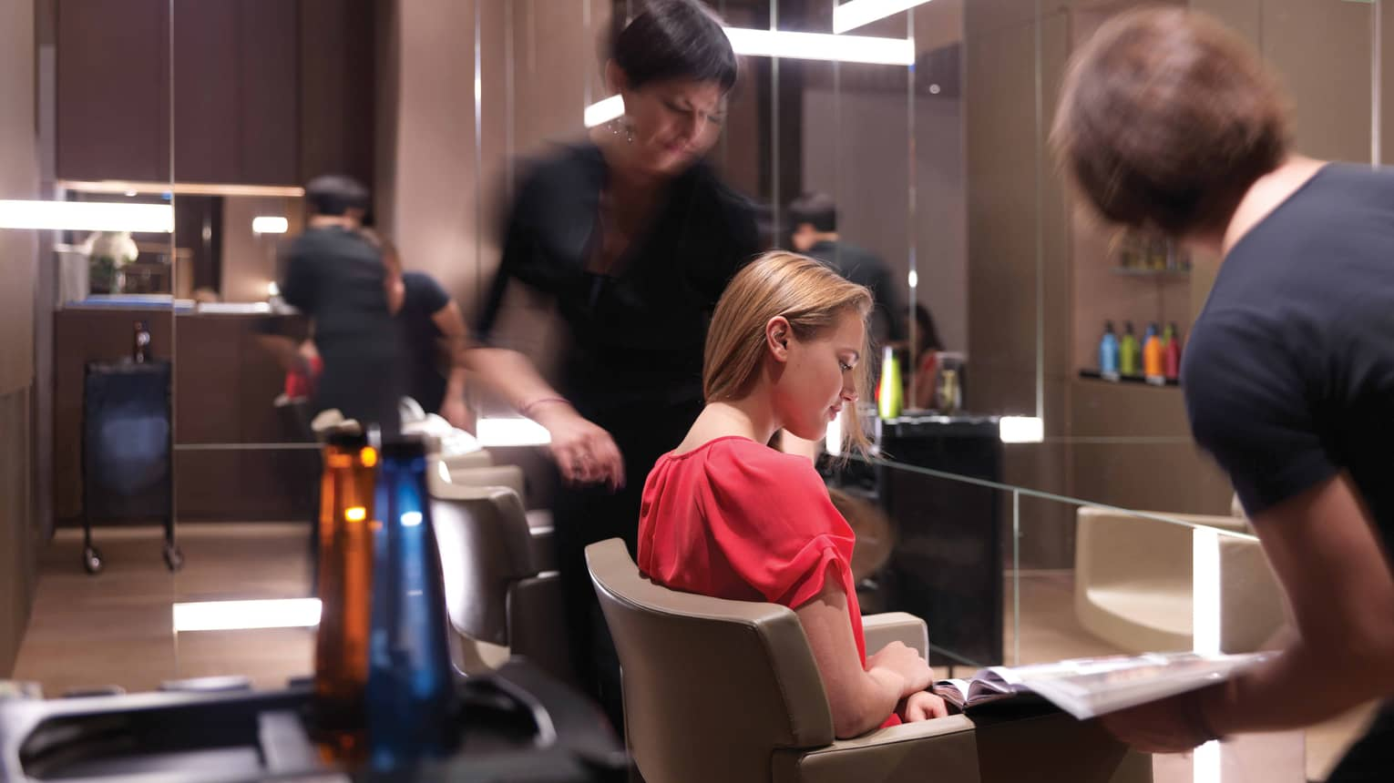 Woman in salon chair at Rossano Ferretti Hair Salon as stylists work around her
