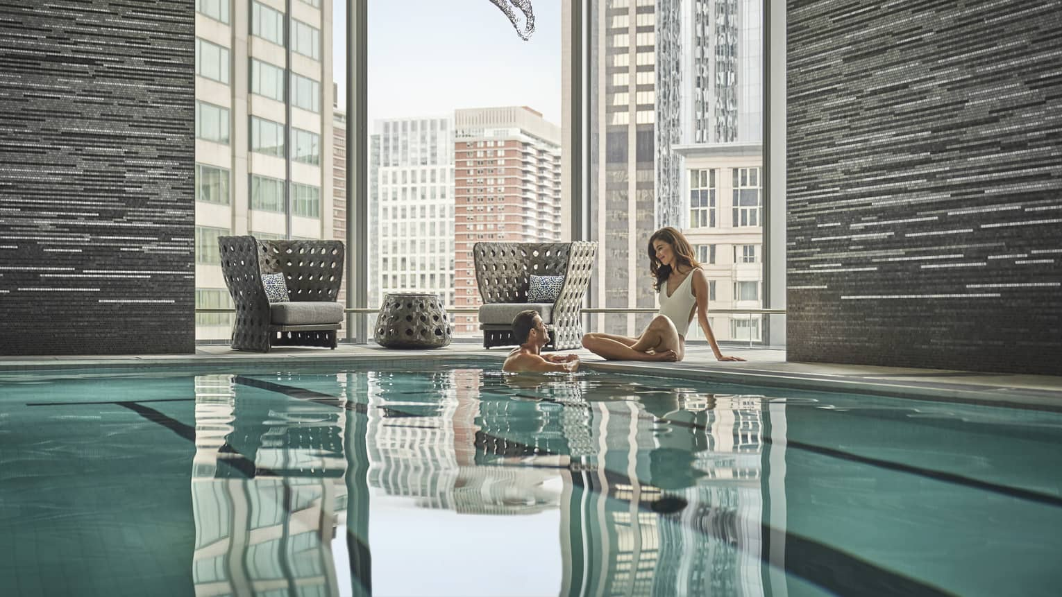 A couple embraces in a lap pool; behind them, floor-to-ceiling windows reveal an urban landscape.