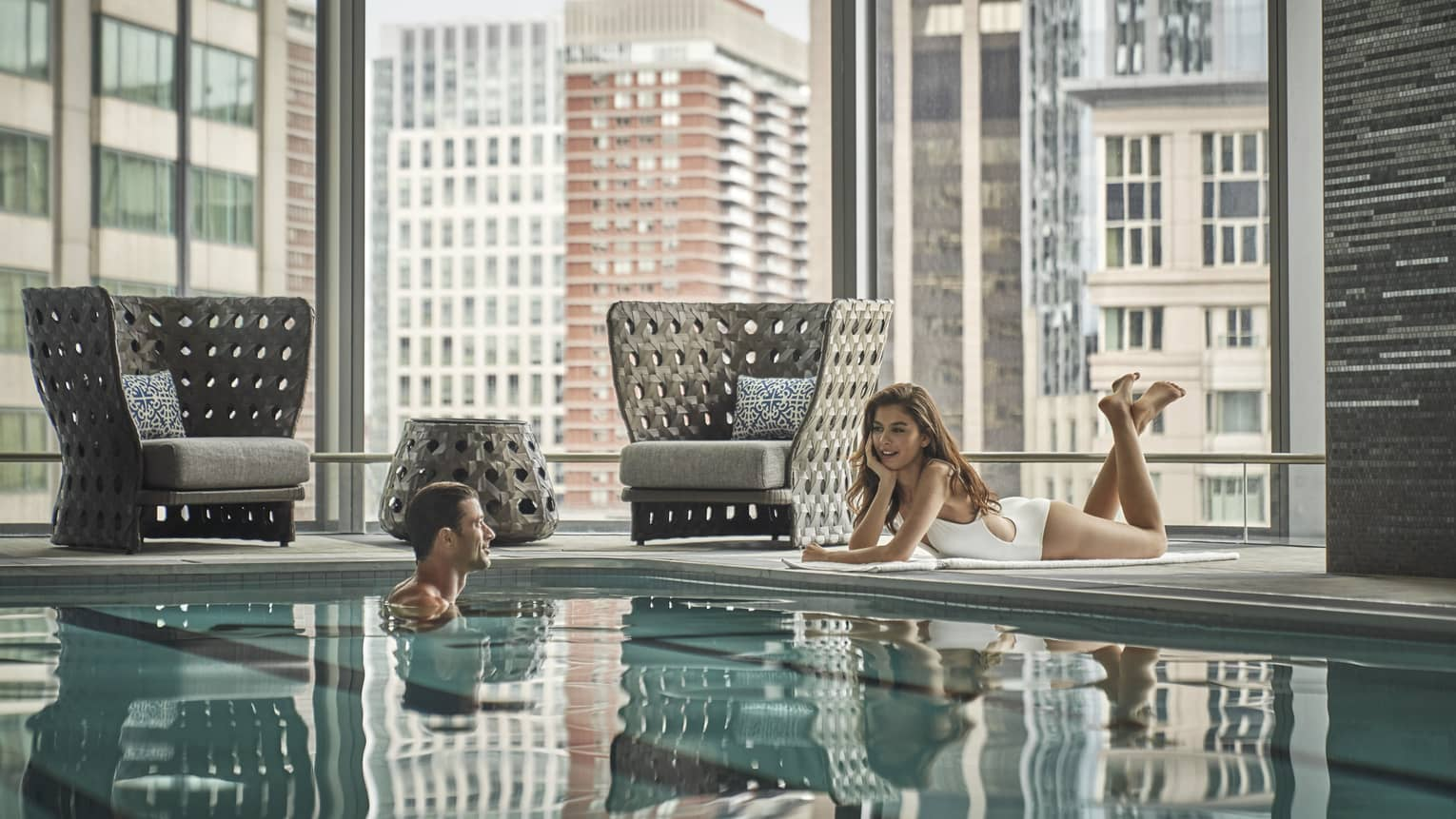 Woman in white bathing suit lounges poolside, talking to a man in the pool with the Boston skyline behind them