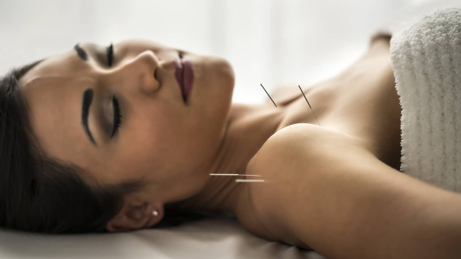 Side of woman's face, eyes closed, as she lies on massage table in spa
