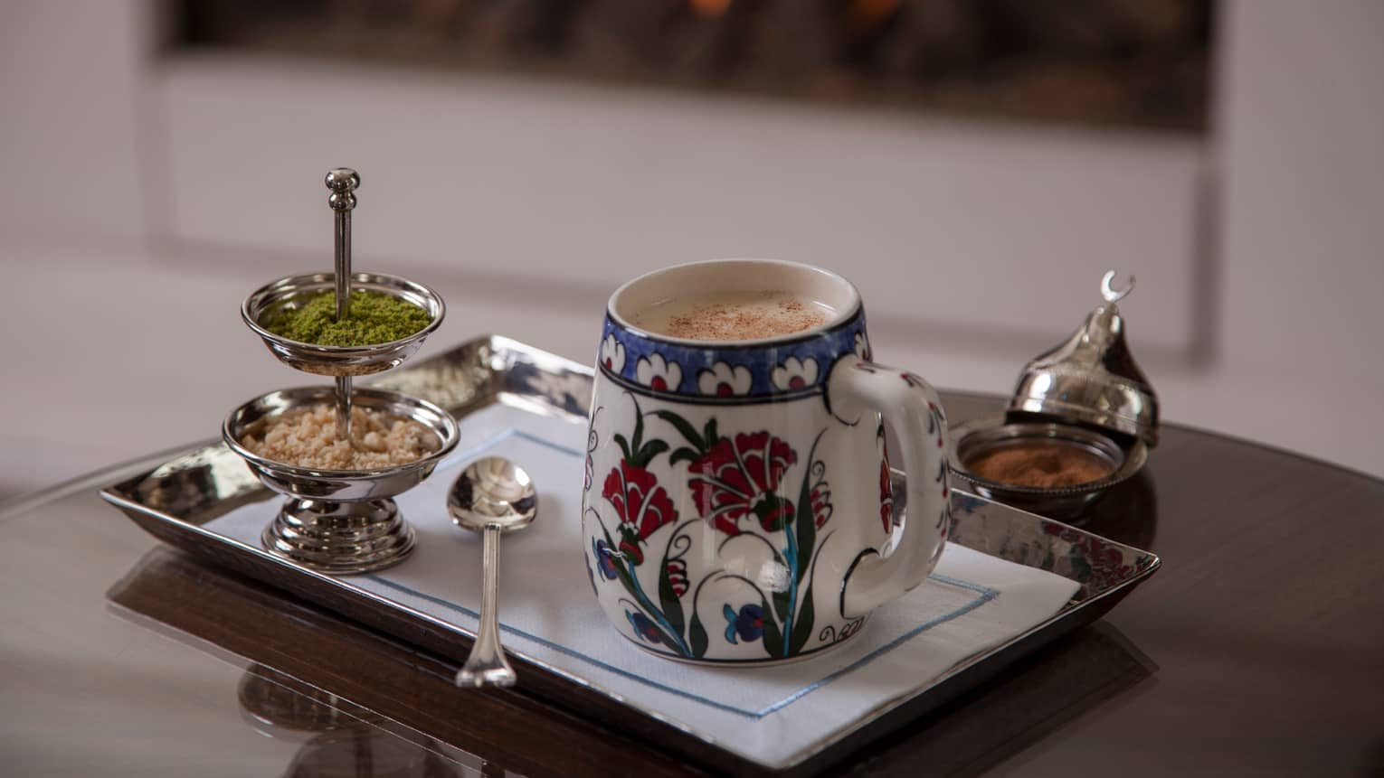 Frothed hot drink in decorative cup on tray with silver garnish dish, spoon