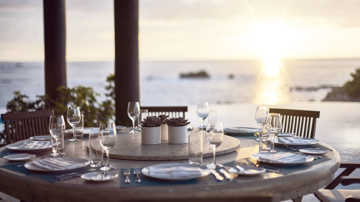 Round outdoor dining table with wine glasses, ocean and sunset in background