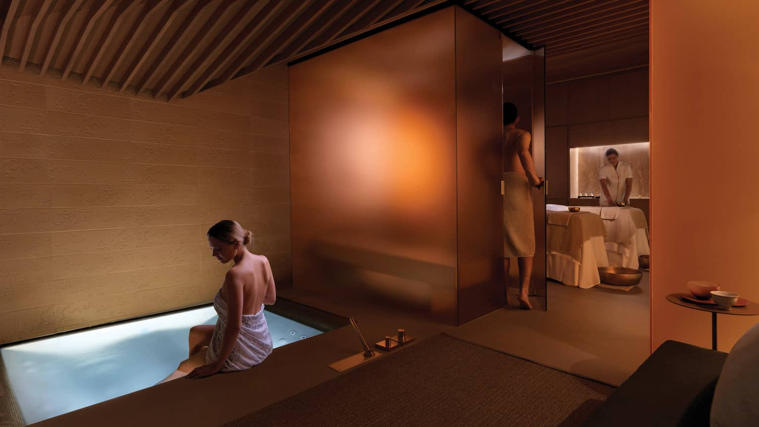 Couples Suite, woman in towel dips feet in small spa tub with lights, man enters glass shower