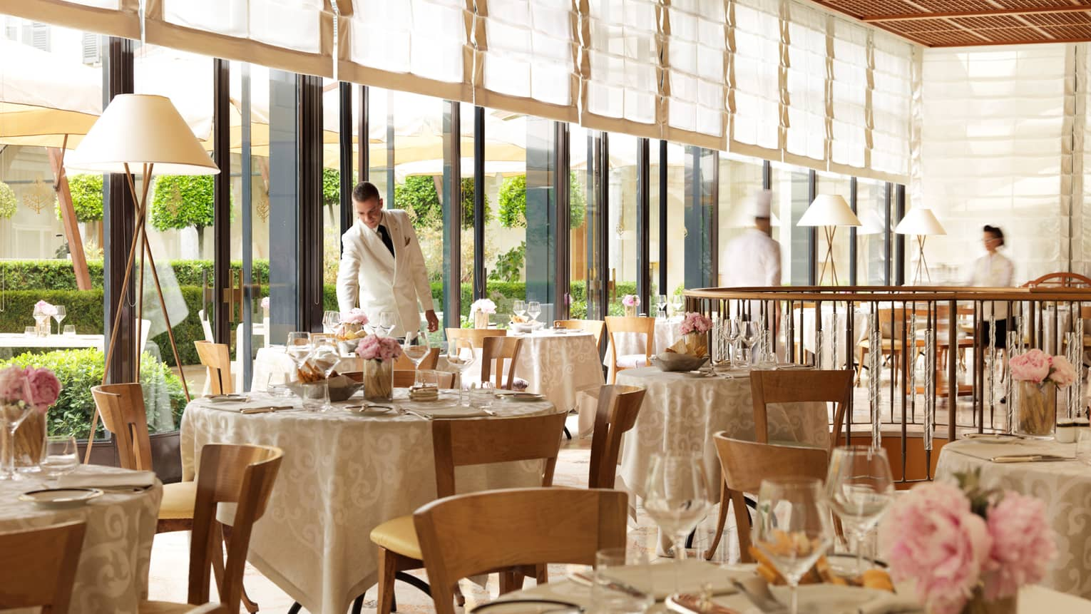 Server wearing white suit sets table in sunny La Veranda dining room, wall of windows