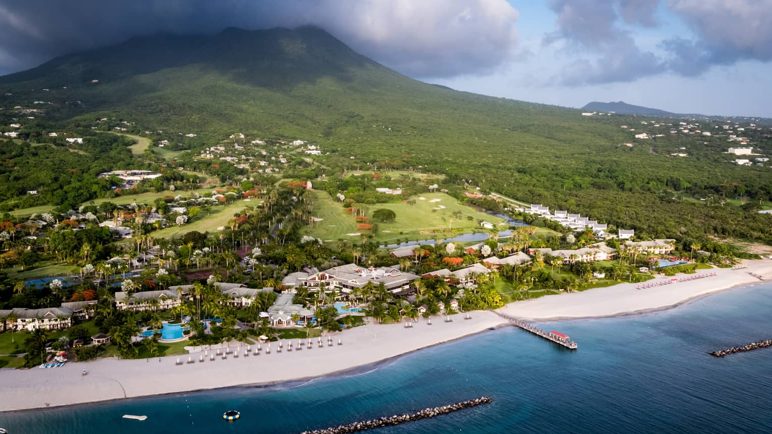 Aerial view of Four Seasons Resort Nevis beach, buildings, green mountain