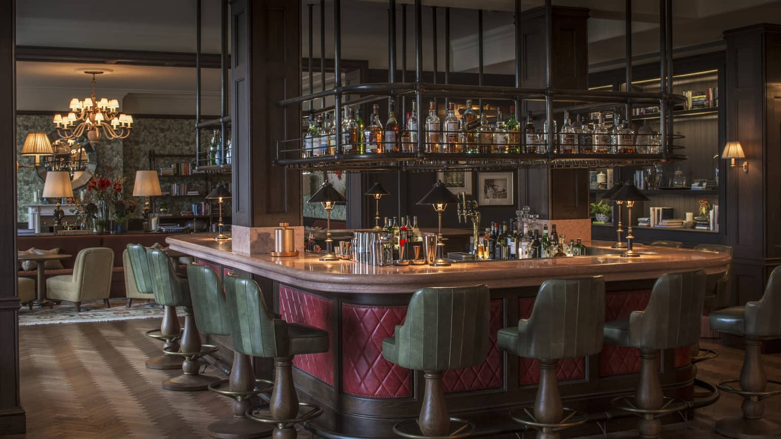 The Bar at Wild Carrot with red-wrapped and wood-accented bar, green barstools, and suspended spirits