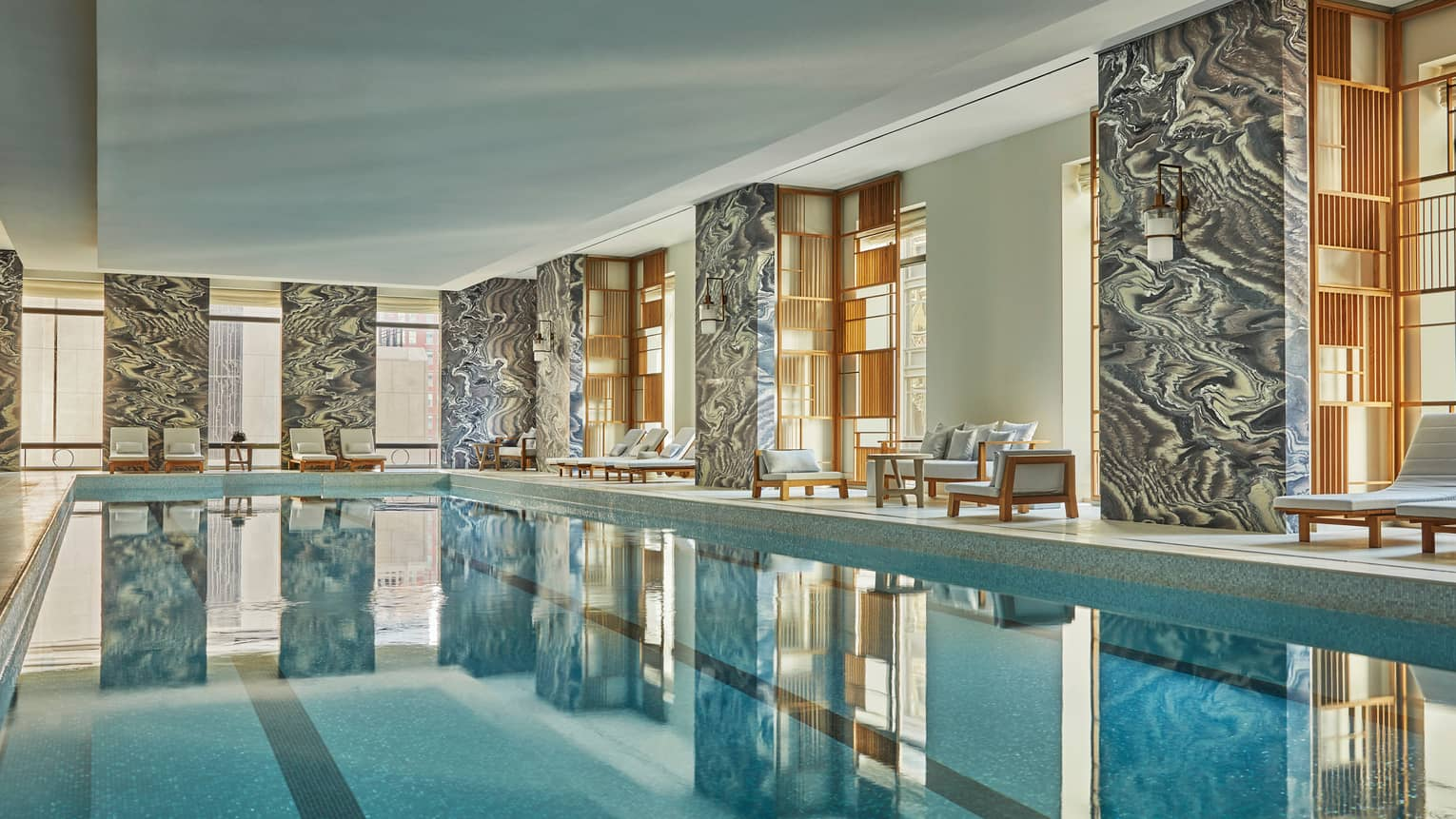 Black-and-white dramatic stone marble pillars, windows around long indoor swimming pool