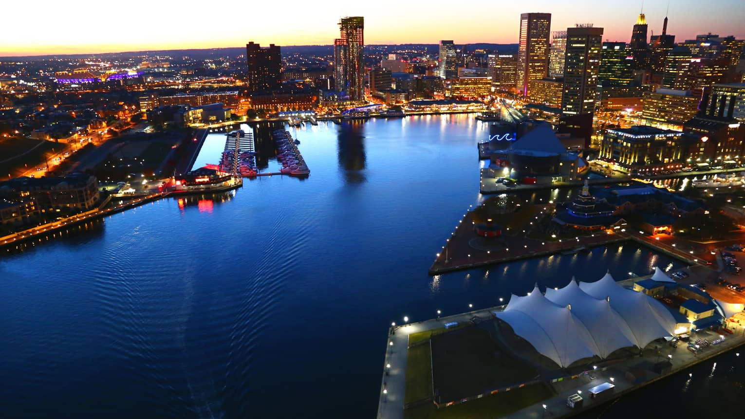 View of the harbour in Baltimore at dusk, surrounded by city lights