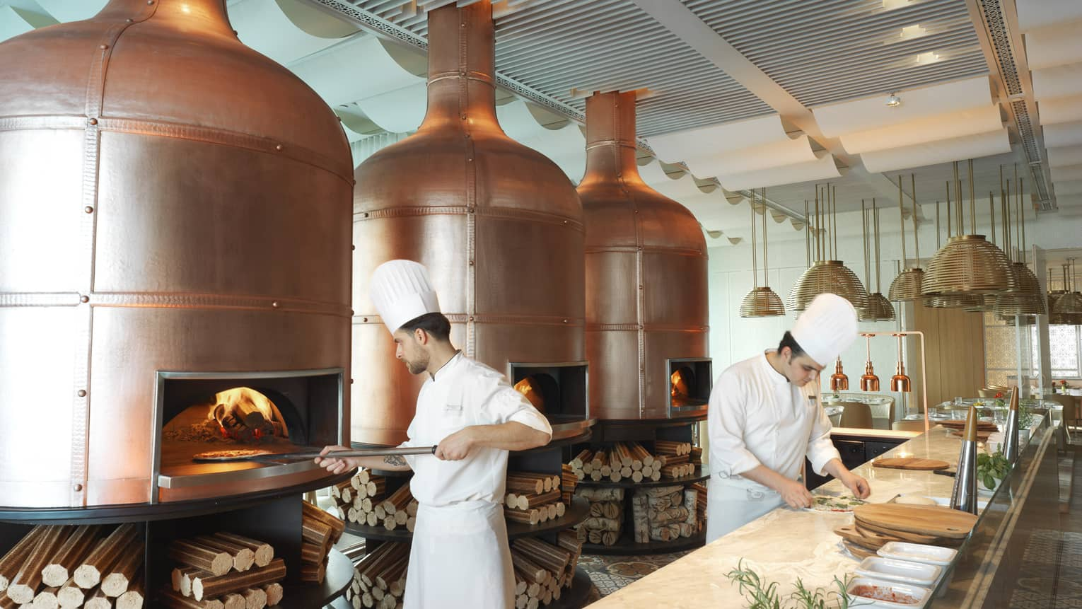 Chef in white uniform, holds wood paddle with pizza in front of three large brass wood-burning ovens