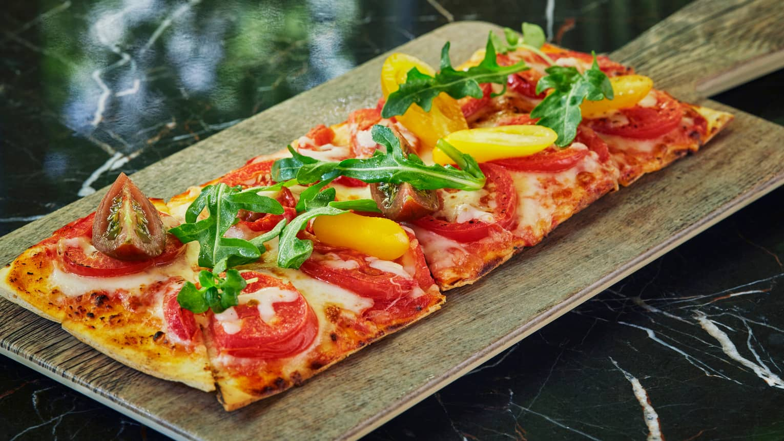 Wood-fired Flatbread pizza topped with tomatoes, fresh greens on wood board