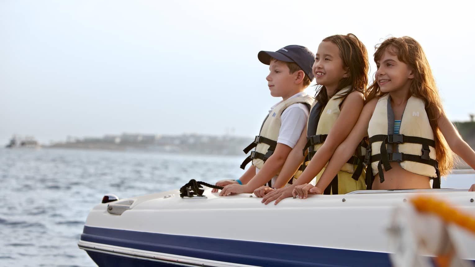 Three children in lifejackets in front of boat smile, look out on water