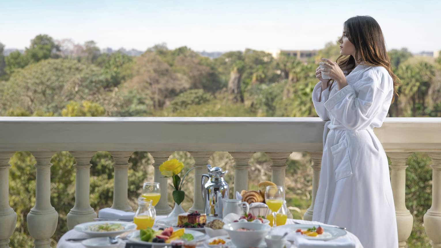 A woman in a white robe sips coffee while looking over a balcony, a variety of food on a table in front of her