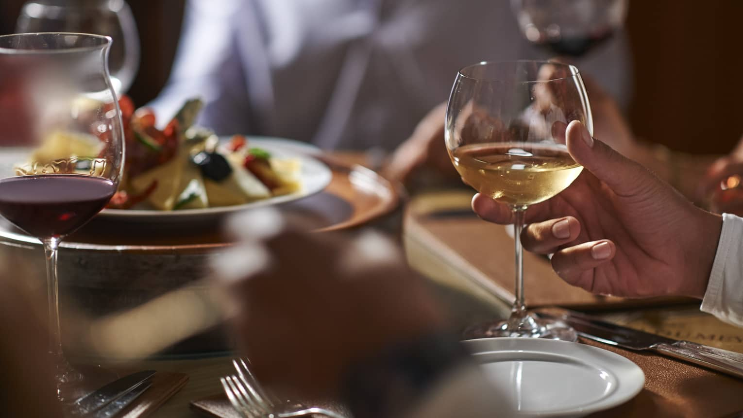 Close-up of hand holding wine glass by dinner plate on table