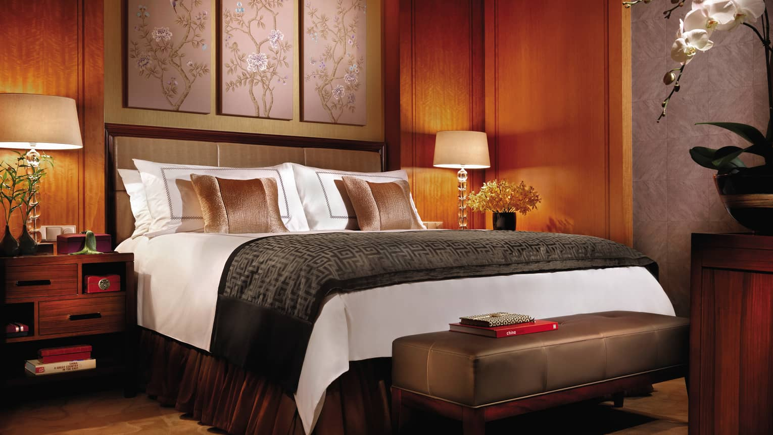 Deluxe Room hotel bed with dark brown, wood decor, traditional Chinese art