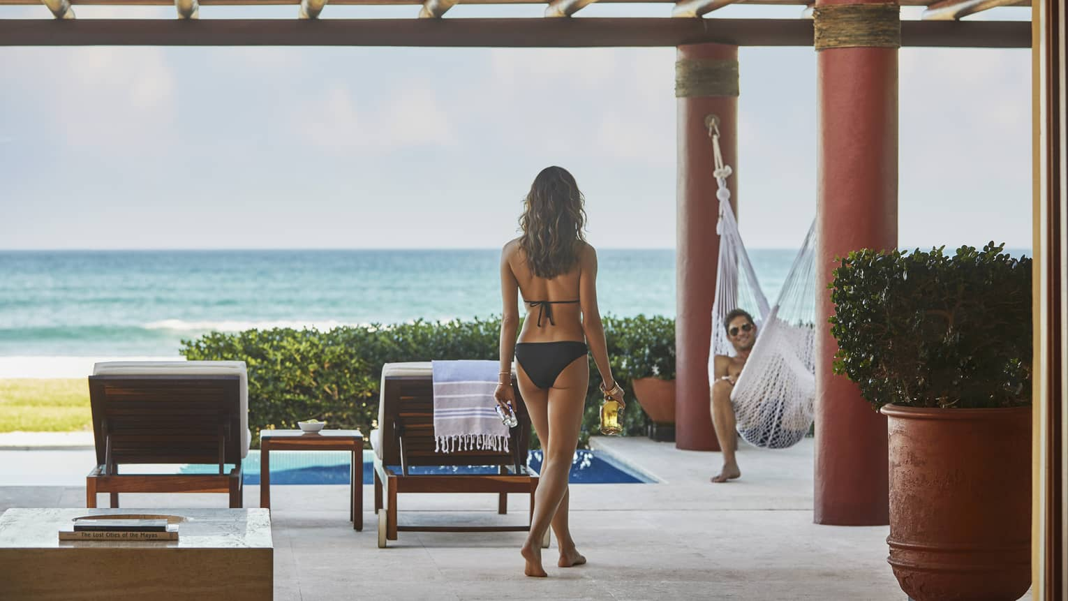 Back of woman in bikini walking along patio to man lounging in hammock
