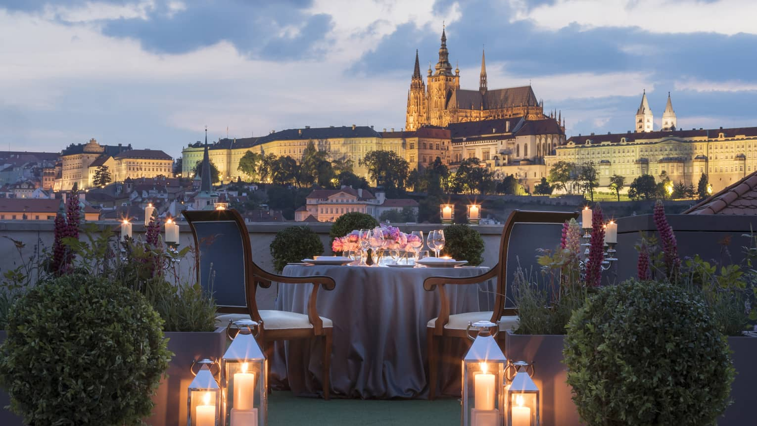 Romantic rooftop dinner with glowing candles and lanterns, overlooking Prague at dusk