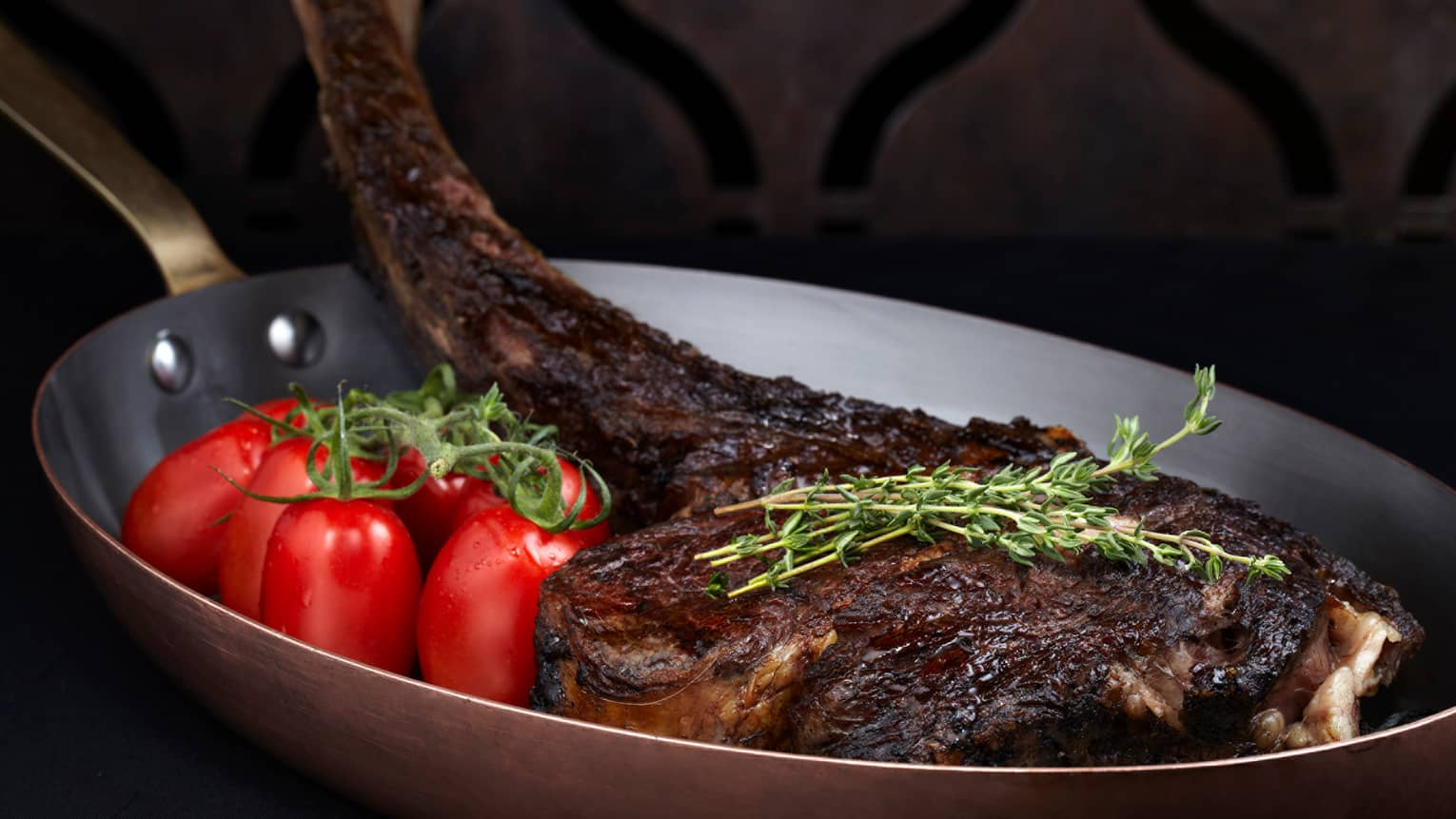 Wagyu beef tomahawk 30 ounce grilled chop in pan with whole tomatoes, herbs