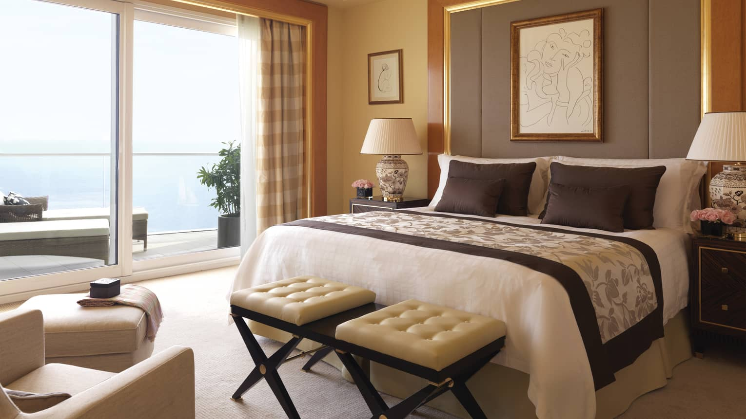 Diplomatic suite room with bed with tall upholstered headboard, bench with two white leather seats, white ottoman