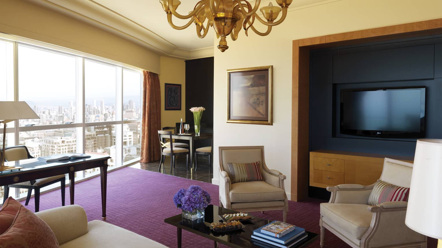 Residential Suite living room with sofa and two chairs, coffee table, purple carpet, large TV, dining table in view