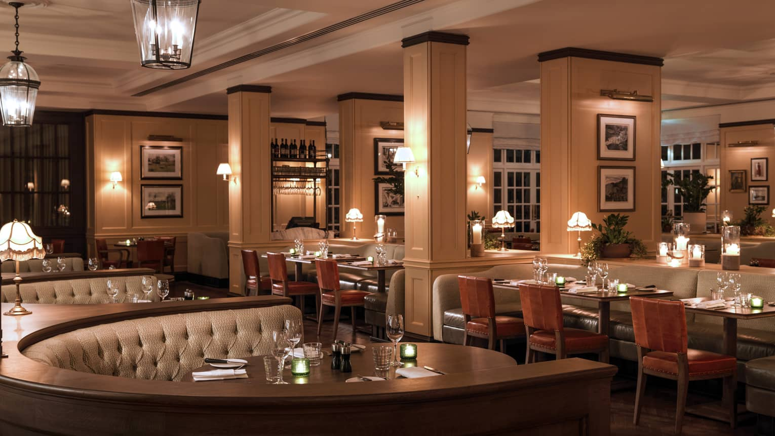 Large curved booths behind tables, chairs in dimly-lit dining room