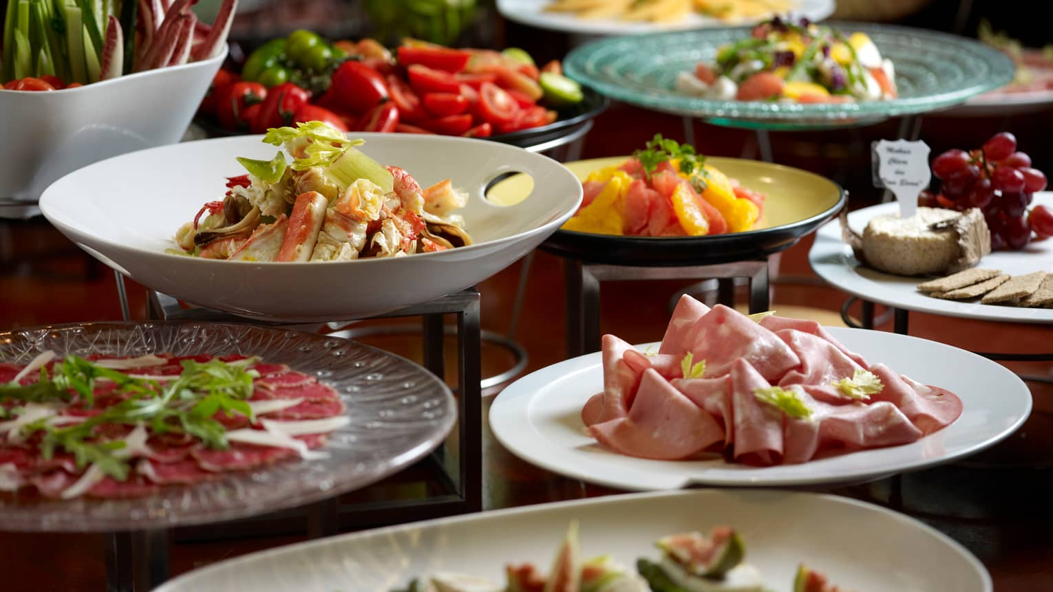 Buffet table with bowls of fresh fruit, salads, deli meats, cheeses