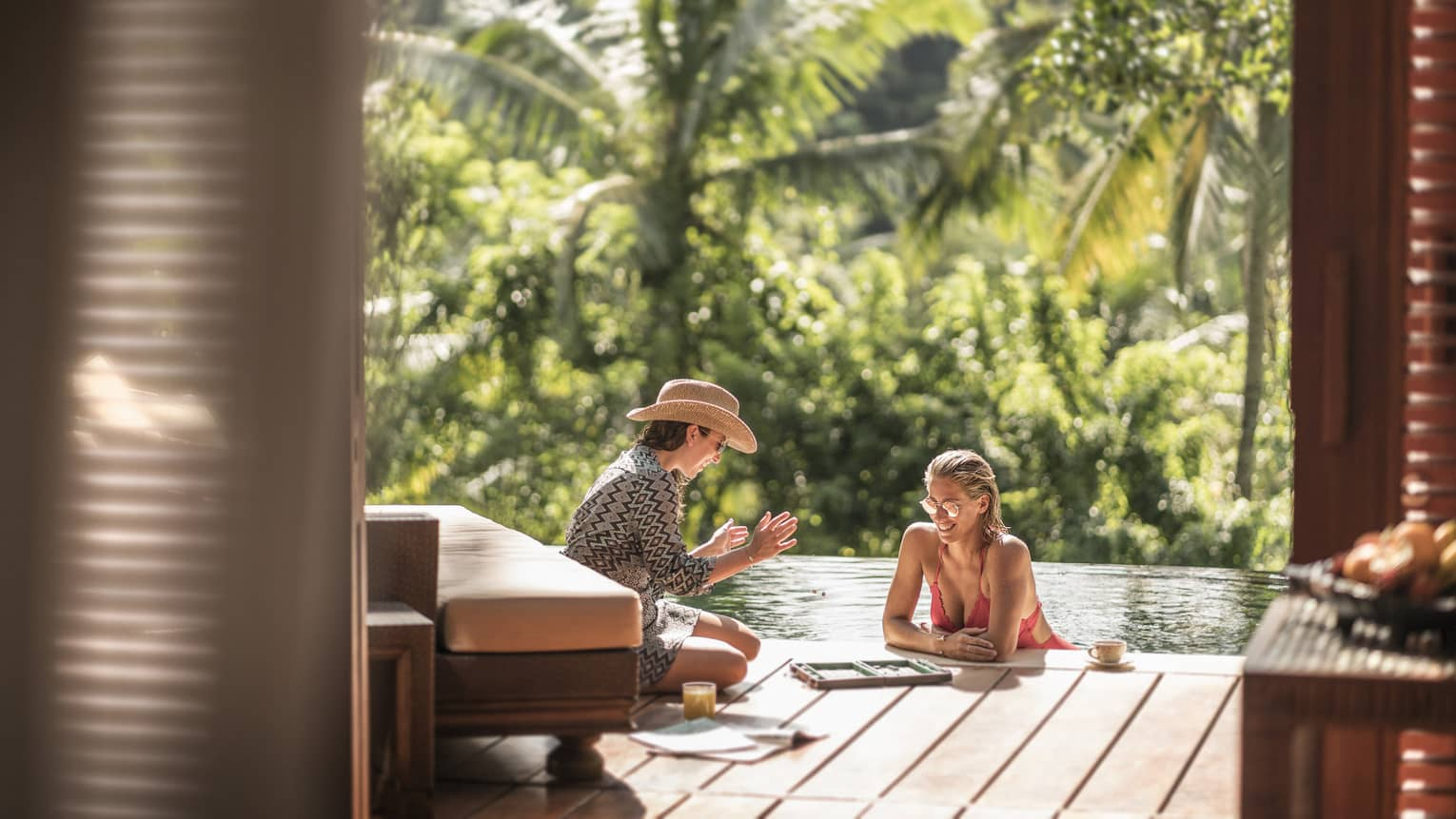 Two guests relaxing and conversing in an outdoor pool in Bali