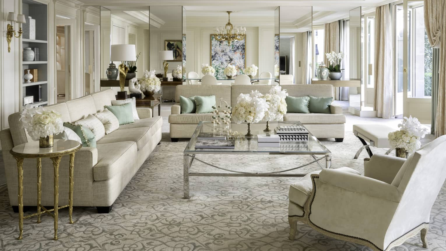 Royal suite with two couches, an armchair, coffee table, cream & teal accents, natural light