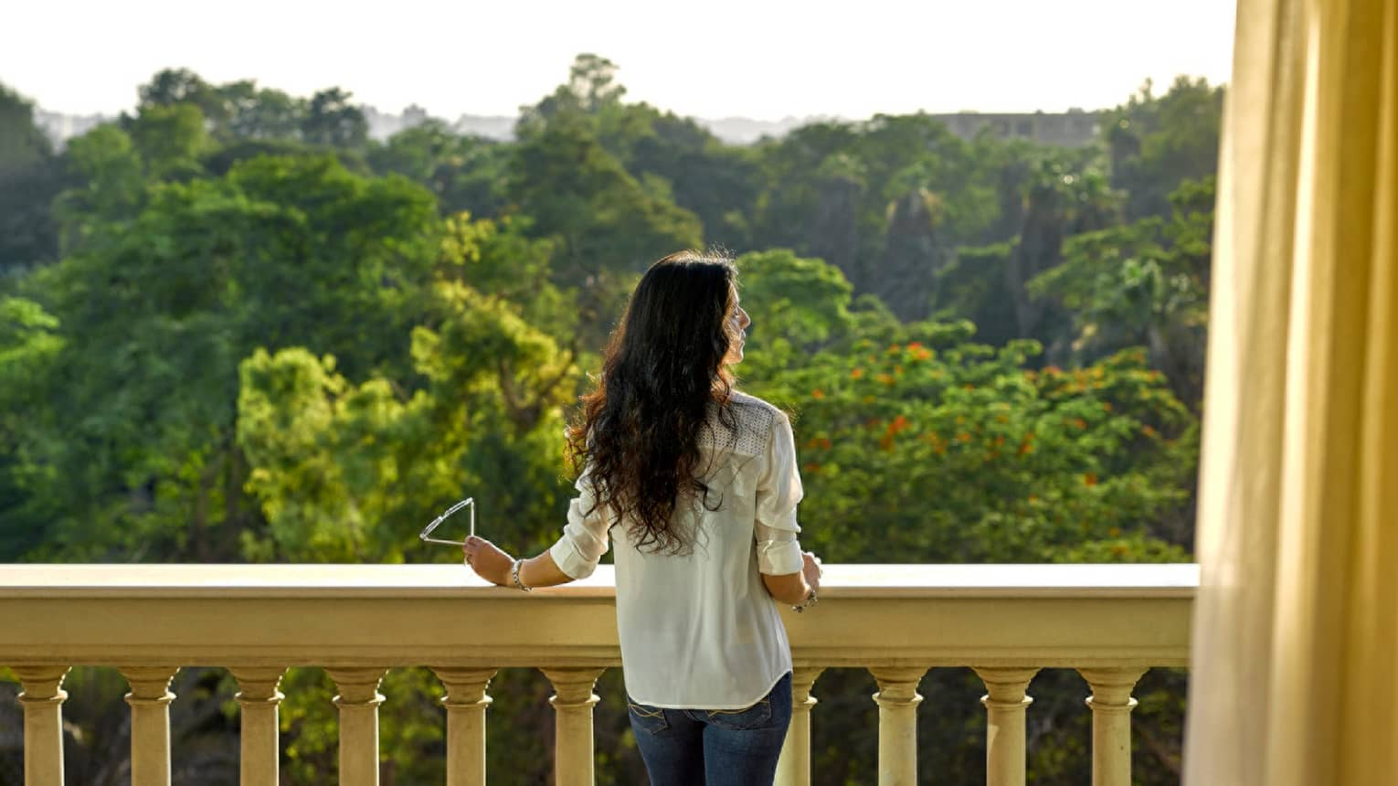 Woman in jeans, button-up shirt looks out over balcony at green zoological gardens canopy