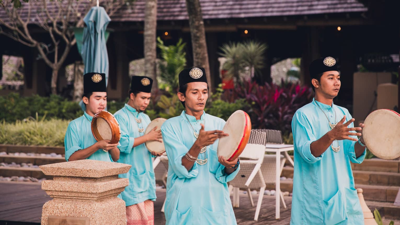 Group of men walk with Kompangs traditional hand drums