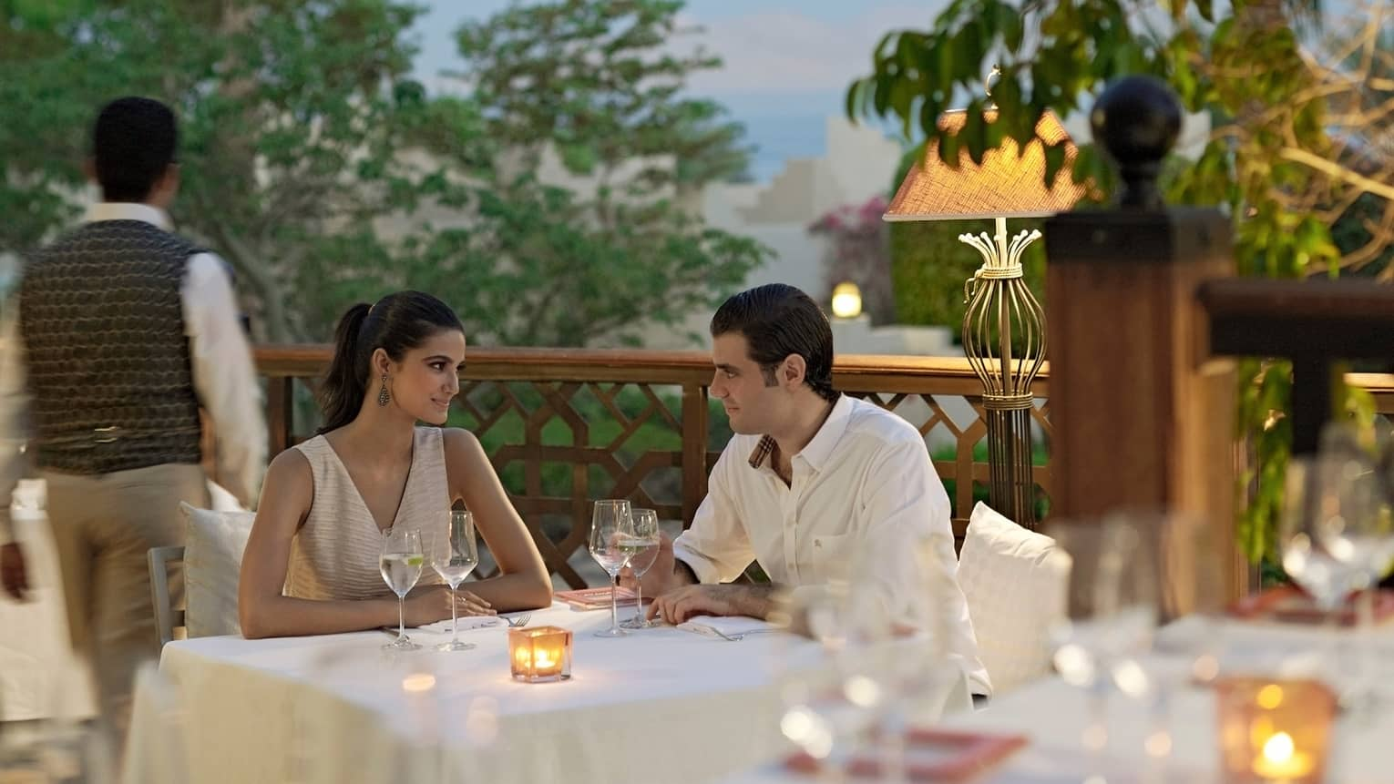 Man and woman at formal dining table on patio at night
