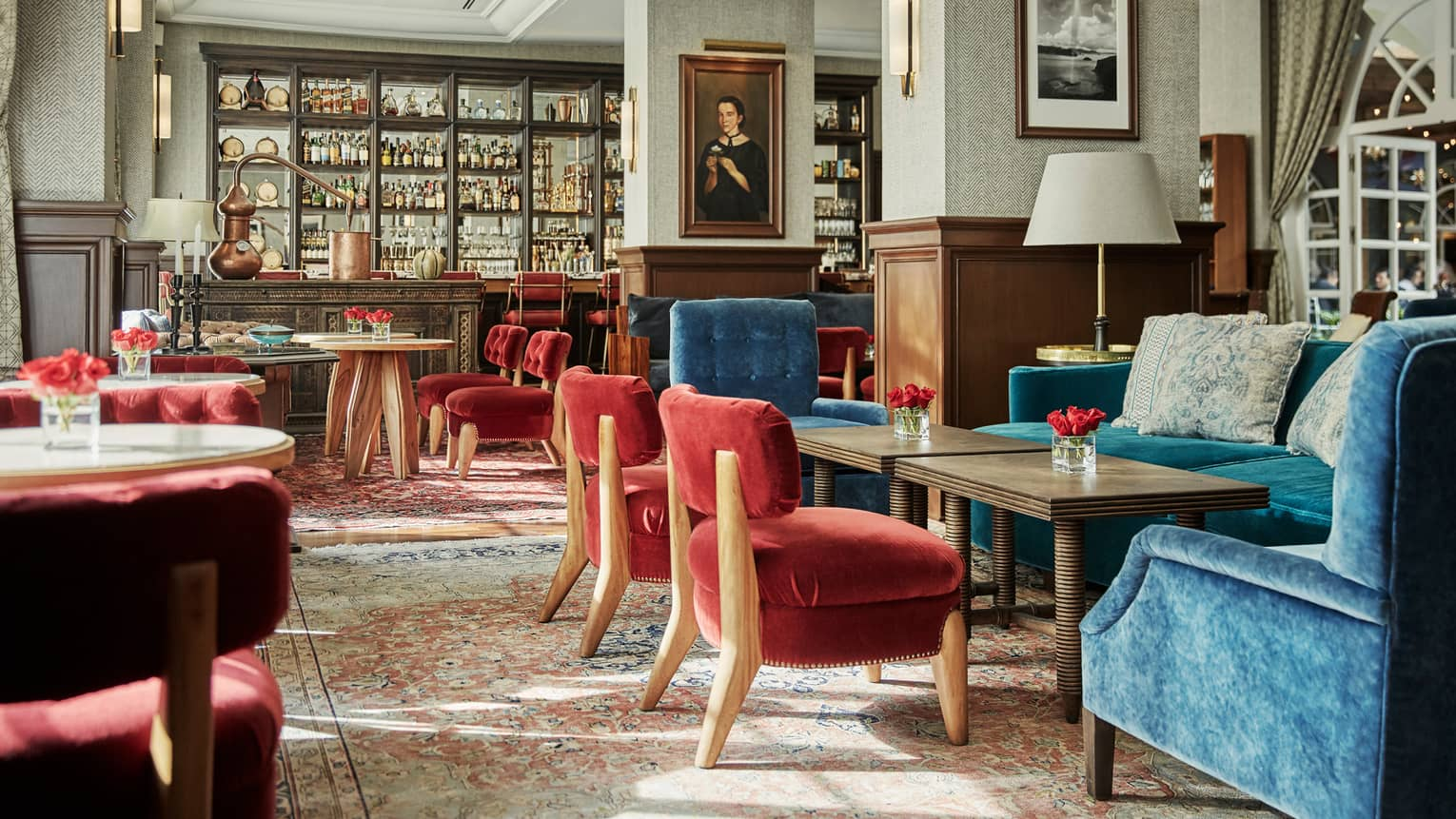 Fifty Mils dining room with red and blue velvet chairs, tables, antique-style bar, framed oil portrait