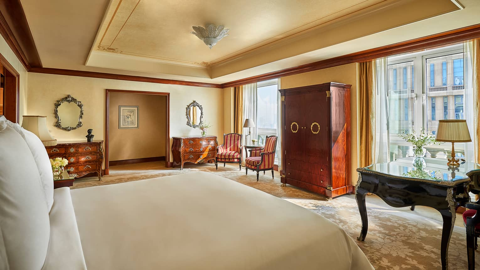 Hotel room bed across from two sunny floor-to-ceiling glass doors, antique-style wood dressers, armchairs