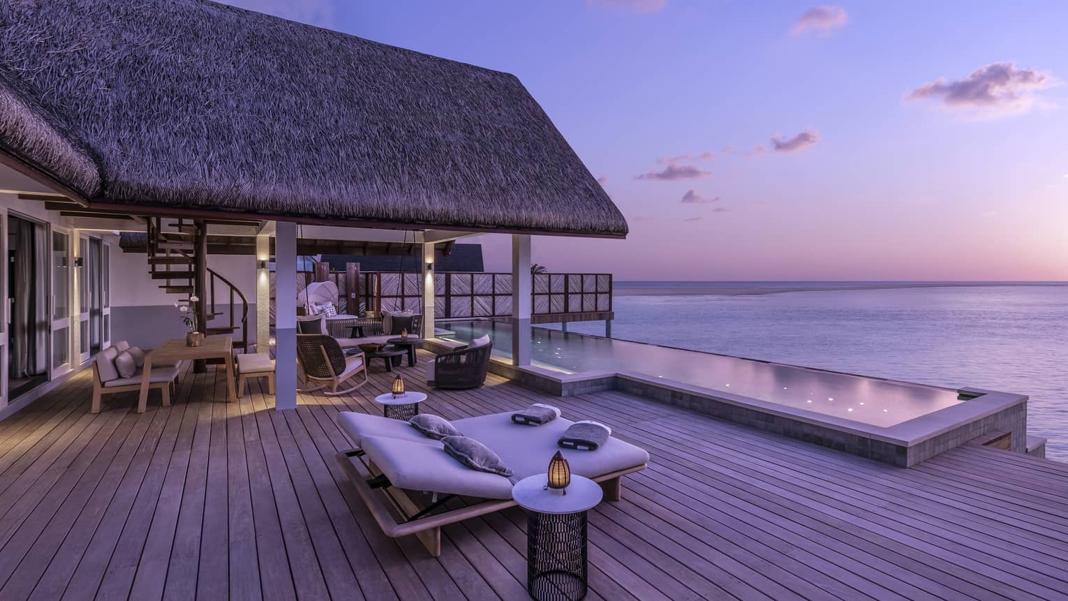 Luxurious overwater bungalow with an expansive wooden deck and infinity pool